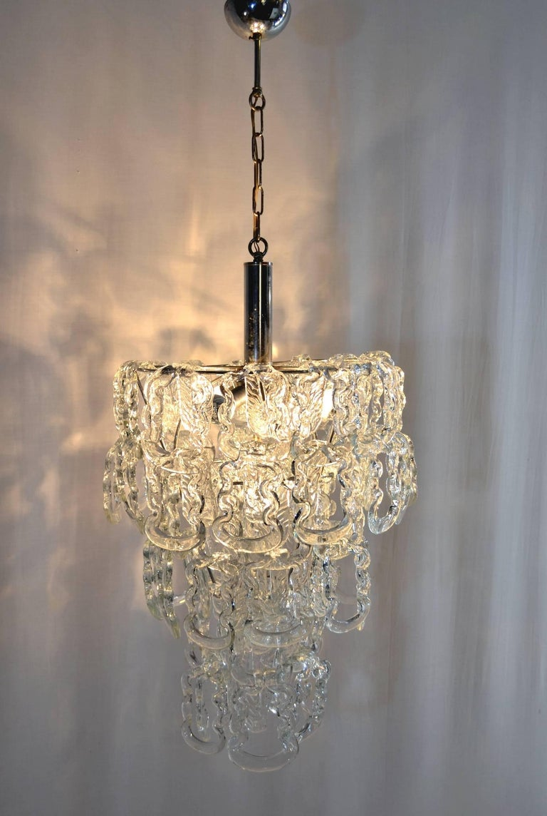 An original three tiered chandelier by Angelo Mangiarotti for Vistosi with Murano glass hanging from a chrome structure. The glass pieces can be hung a bit differently creating different heights for the chandelier. The height in this manner of the