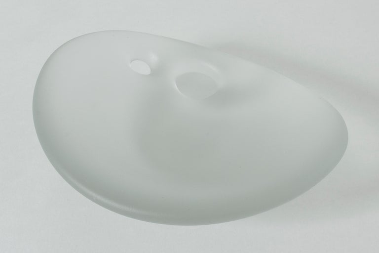"""Beautiful """"Devil's Cradle"""" bowl by Timo Sarpaneva, made in thick glass quality in an organic, rounded form. Two holes close to the edge. Frosted surface."""