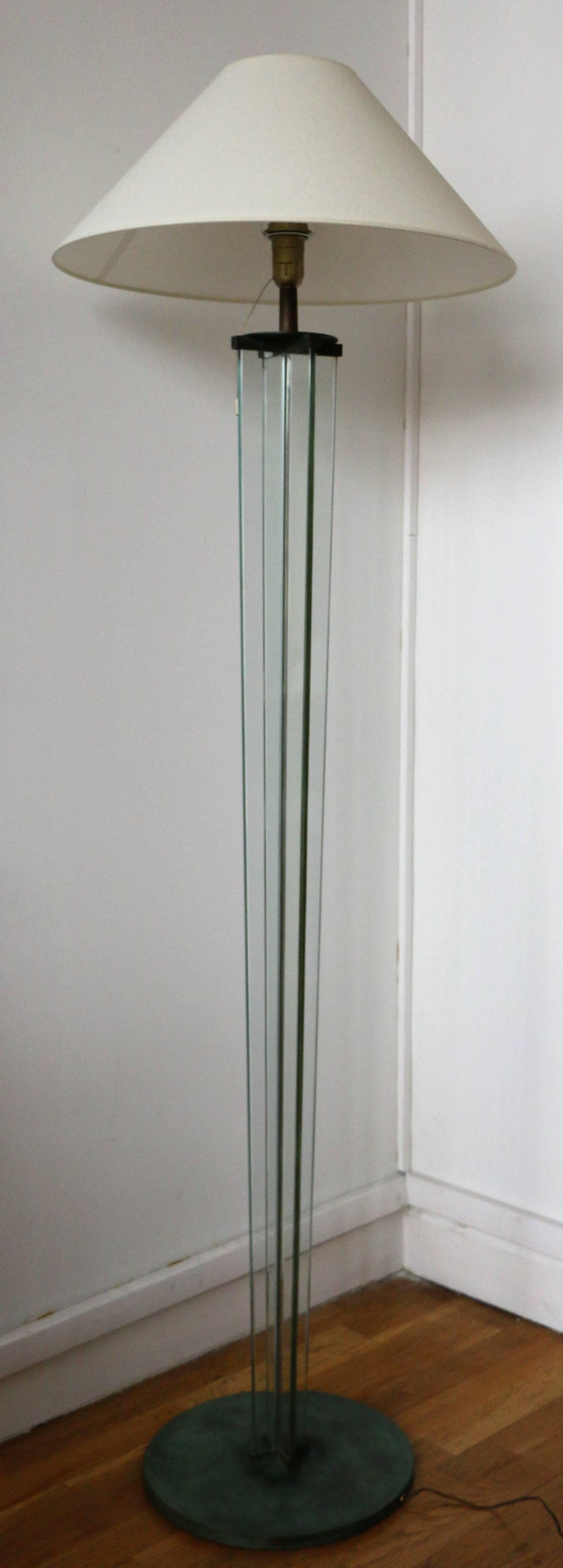 Stunning floor lamp by Jacques Adnet (1900-1984). It has a cross shape and is made of 4 glass panels sitting on an oxidized circular metal base. France, 1930s. Dimensions: height (excl shade): 158cm, base (diameter): 35cm Electrified for European