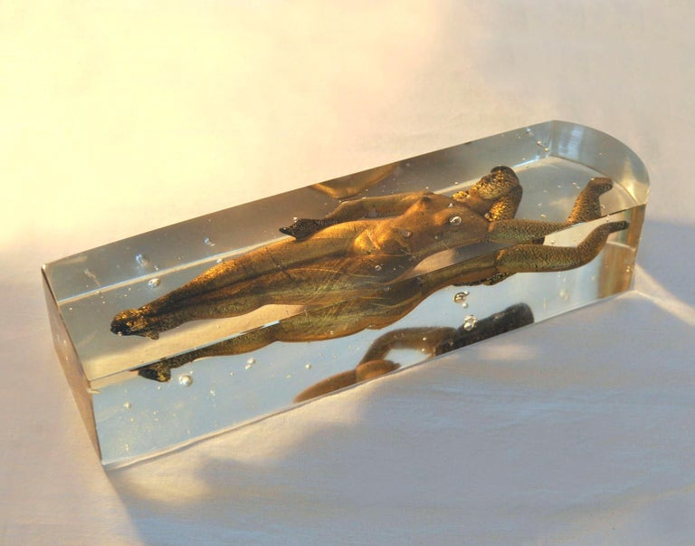 Female torso in glass block paperweight with a nude women in black glass and gold flakes applied over black, floating inside clear glass.