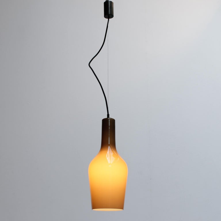 Bottle shaped cased glass pendant by Vistosi, Italy. Dimensions fixture: height 15.4 inches (39 cm), diameter 6.7 inches (17 cm). From ceiling till drop: 55.1 inches (140 cm). The fixture is equipped with an E27 socket - also suitable for E26