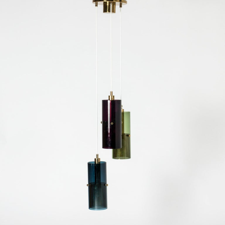 Striking ceiling lamp by Hans-Agne Jakobsson with three cylindrical glass shades suspended from a large brass ceiling cup. Perforated brass cylinders inside enclose the light sources and give a beautiful sheen through the red, blue and green