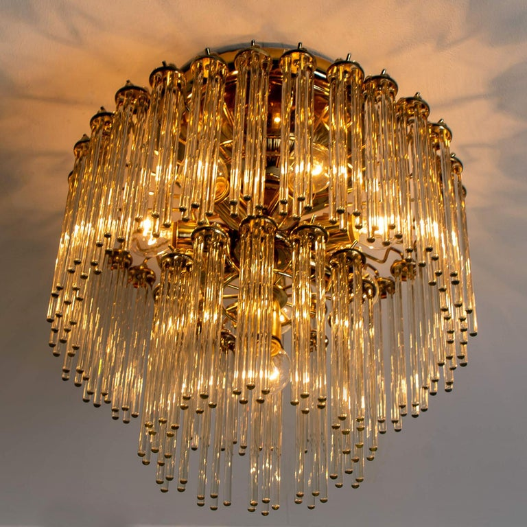 A Italian Mid-Century Modern glass rod and brass Gaetano Sciolari flush mount for Lightolier, circa 1960s-1970s. Illuminates beautifully. With 48 pierced round form clusters of light catching optical quality glass rods (7.1 inch) sitting on a brass