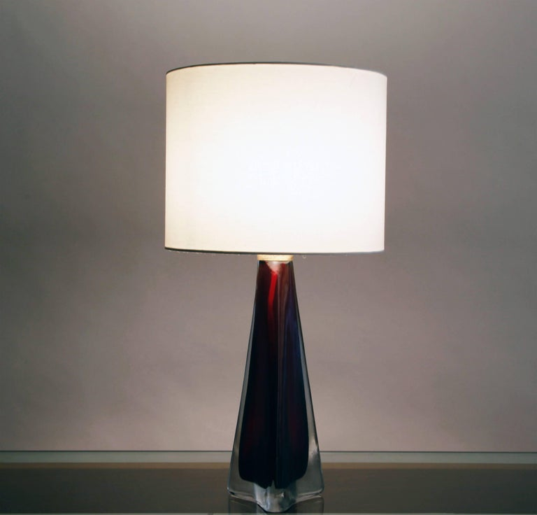 The glass is a rich garnet color, with a narrow patinated brass collar at the top of the base. The linen shade is new, and the lamp has been rewired for the US. Dimensions do not include shade.