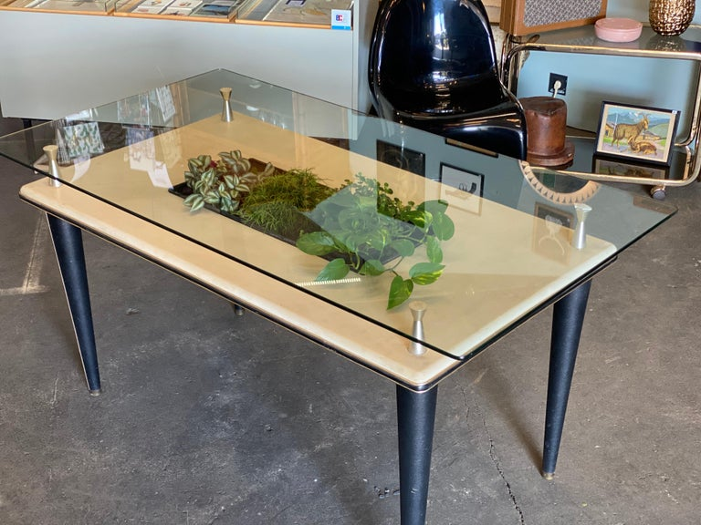This dining table was produced in Italy during the 1950s and features a glass top with a central basin. The top and legs feature skai, as do the edges of the piece in the form of a trim around the border. The glass top and top of the frame are