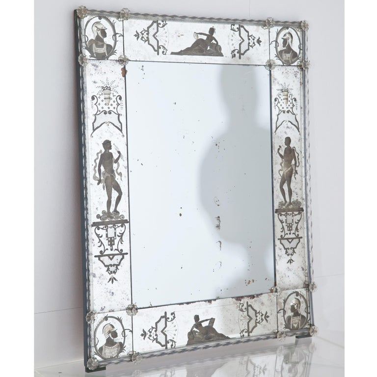 Rectangular wall mirror with a narrow frame and floral decoration out of glass and etched figure decorations around the edge. The mirror glass is blind in places.