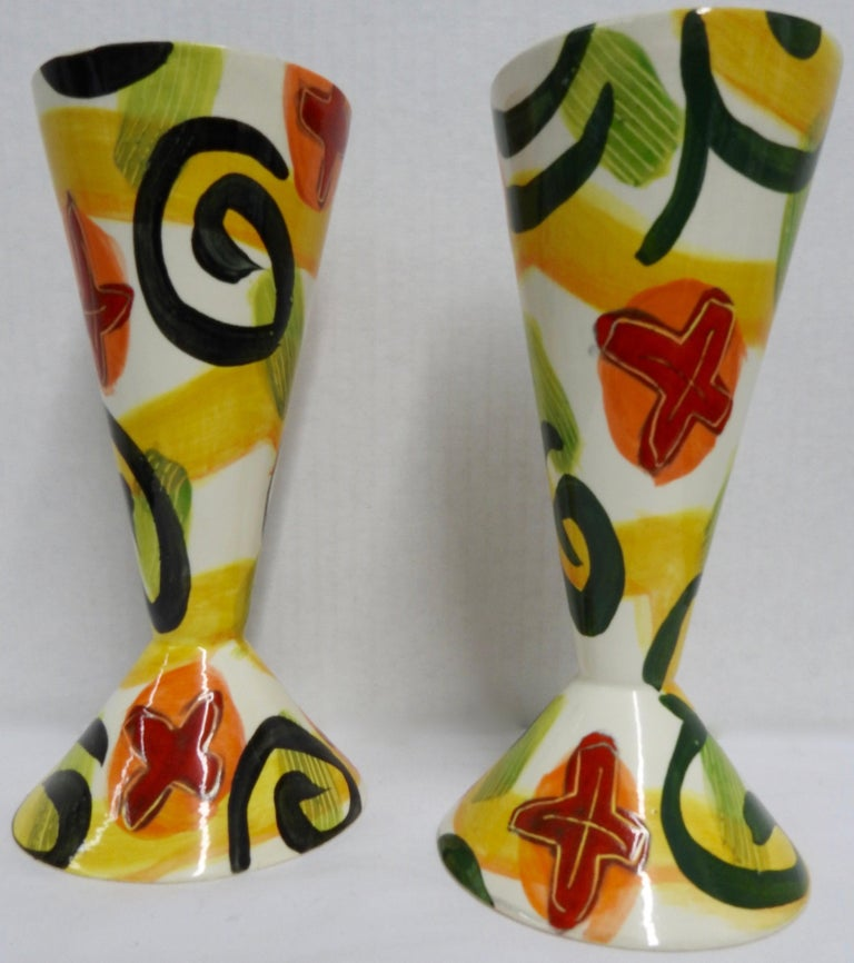 Bold shades of red, orange, yellow and green on white compliment this pair of whimsical goblets by ceramic artist Marilee Hall. The inside is glazed in shiny black. Both goblets are signed on the bottom.