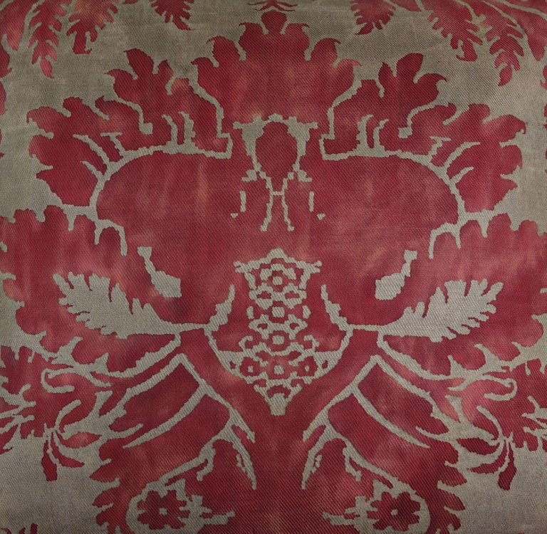 Pair of custom pillows made with vintage Glicine patterned Fortuny fronts and contemporary red velvet backs. The pattern has a wisteria motif in rich colors of red and metallic gold printed on a cotton fabric. Self velvet cord detail around the
