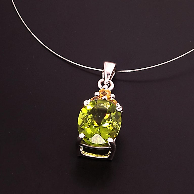 Unique, sparkling oval green Peridot pendant with accents of Yellow Sapphires.  This gorgeous pendant will sparkle and wink as you move.  The 3.85ct  peridot is accented with three Yellow Sapphires with a total weight of 0.37ct. The Peridot and