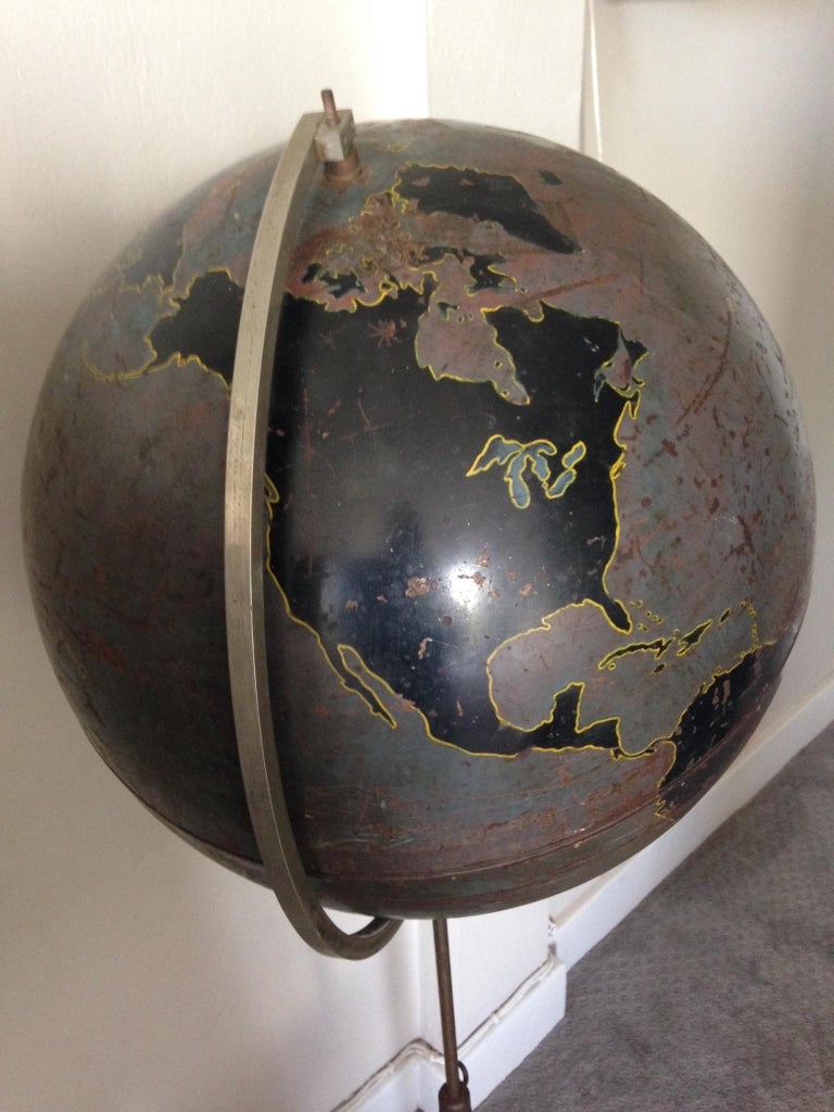 Military globe of steel with heavy, cast iron base by Denoyer Geppert, circa 1920s. Used as aviation training tool by the military, hence lack of identifying information on the land masses. Beautifully worn patina of browns and blacks mounted on