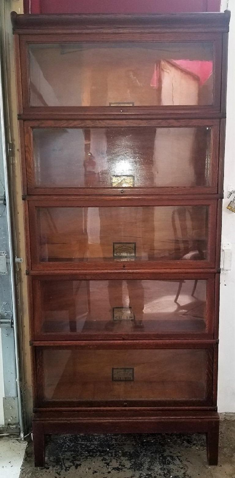 Presenting a rare early 20th century Globe Wernicke 5-section barristers bookcase.  From circa 1910 and made of dark oak with boxwood lining in each drawer.  5 detachable sections on a solid footed base and pelmet top.  Each section has a