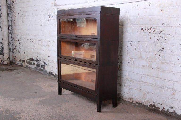 A very nice antique mahogany three-stack barrister bookcase by Globe-Wernicke. The bookcase has a beautiful mahogany finish. Each glass front door opens and closes smoothly and has plenty of room for storage. It comes apart in five sections,