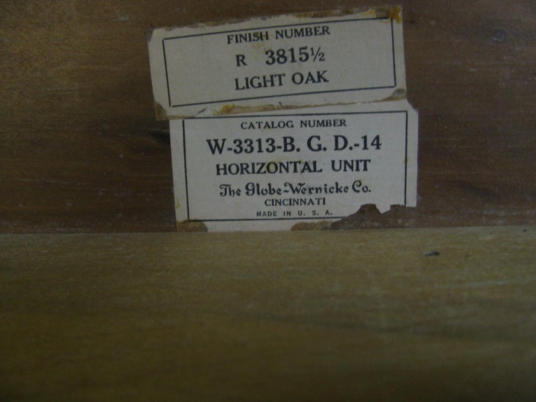 Fabulous 5 section oak stacking bookcase by Globe Wernicke. 3 sections for storage measuring 14.75 each, with atop and a bottom to complete the set. Original glass and brass knobs, paneled sides.
