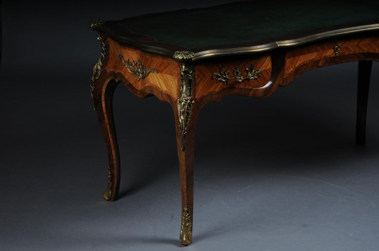 In Bois-Satiné veneer, all-around mirrored veneer with rocaille applications. With extremely finely chased, very decorative, restrained bronze fittings framed. Rosewood veneered on solid beech wood. Heavily domed, four-sided curly, three-legged base