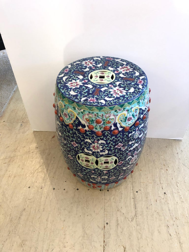A magnificent intricately detailed ceramic garden seat having a melange of colors including navy blue, white, turquoise, pink and Chinese red. Makes a wonderful side or occasional table.