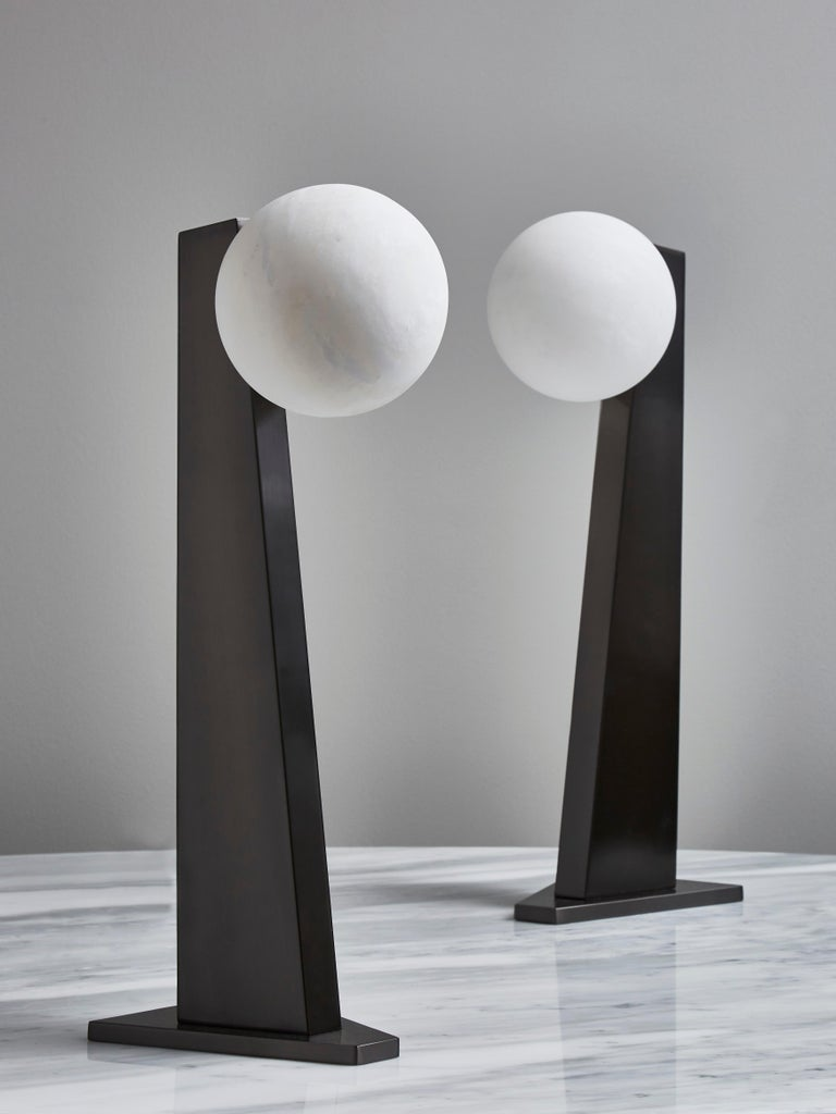Table lamp version of our popular floor lamp, asymmetrical brass foot in black nickel satin finish holding a single alabaster globe.  Designed by Glustin Luminaires  Price displayed per table lamp.