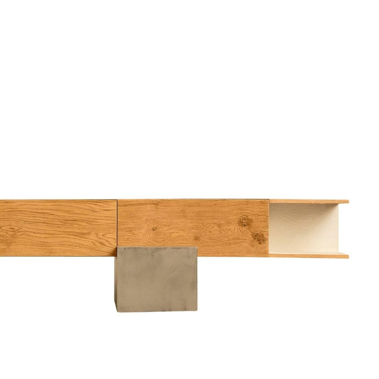 This well crafted oak beam storage unit by Giacomo Moor balances on an off centre concrete support. The cabinet has three closed compartments. Two doors fold downward, and one folds upward, and an additional storage shelf has a white varnished