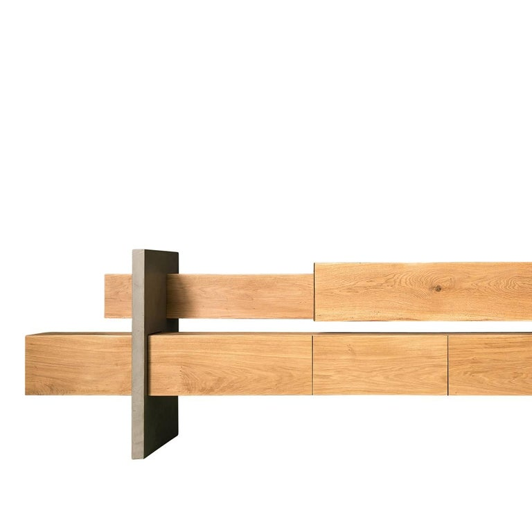 Within this oak and concrete sideboard by Giacomo Moor are six unevenly arranged storage compartments. In the lower beam there are two swinging doors, a double depth drawer, and a drawer and a white varnished compartment. In the top beam, there are