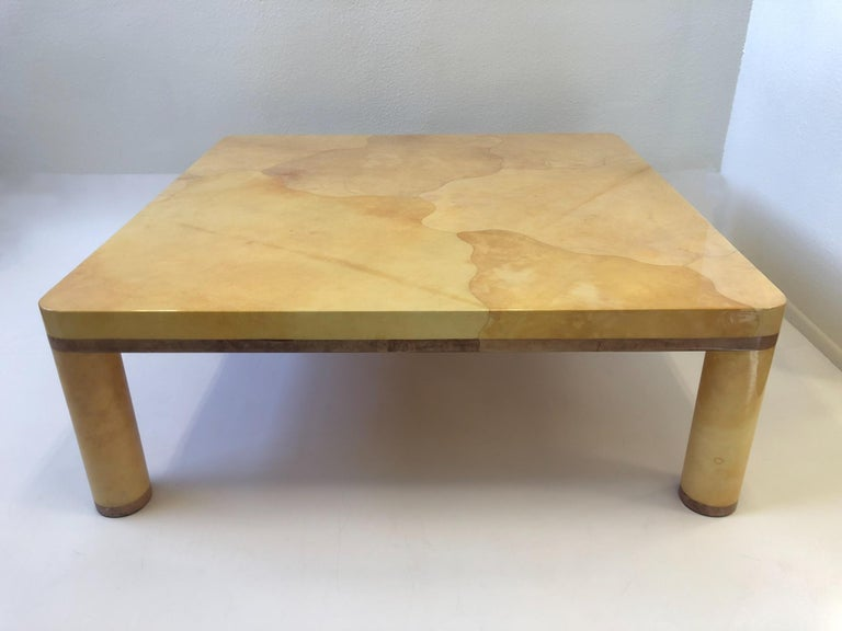 A spectacular 1980s goatskin coffee table designed in the style of Karl Springer. The table is constructed of wood that's covered with natural goatskin and a light purple stained goatskin edges the table does have a minor repair on one of the