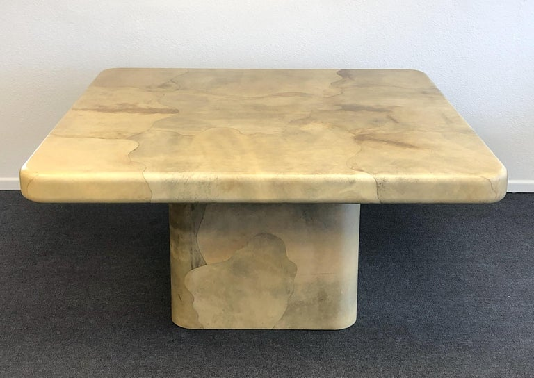 A amazing goatskin dining table design by renowned designer Karl Springer in the 1980s. The table it's constructed of wood that's covered in goatskin and then lacquered. The tops underside is covered in goatskin also. The table is in beautiful