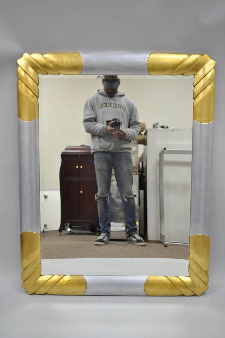 Vintage gold and silver leaf Hollywood Regency / Art Deco style wall mirror by Turner. Item features a gold and silver leaf finish, bevelled glass, molded foam frame, impressive stylish form, original label to rear. Can be hung vertical or