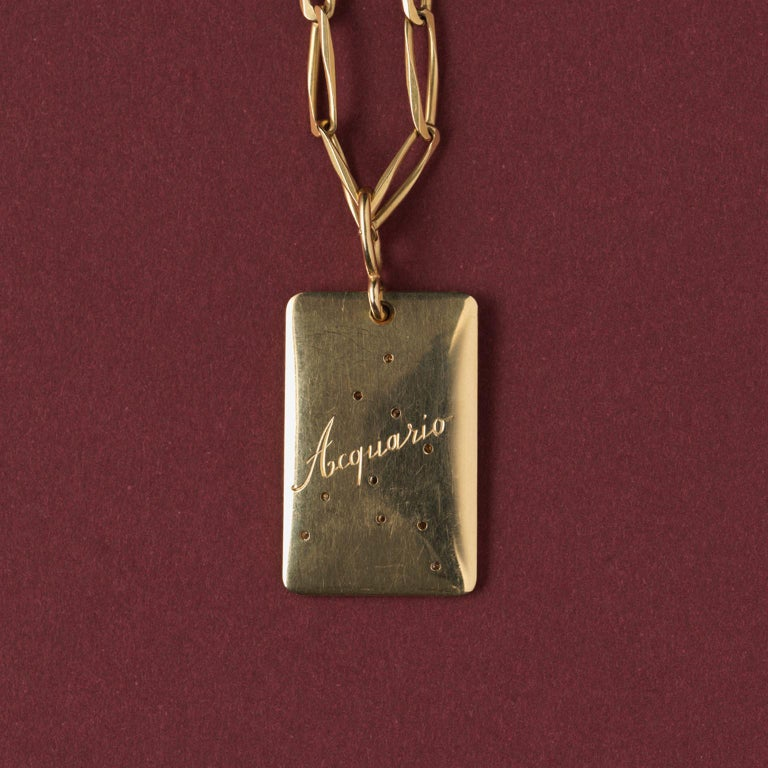An 18 carat gold rectangular pendant with the aquarius sign set with diamonds, on the reverse engraved: Aquario, Italian maker, circa 1970.  weight: 18.11 gram dimensions: 4.2 x 2.0 cm.