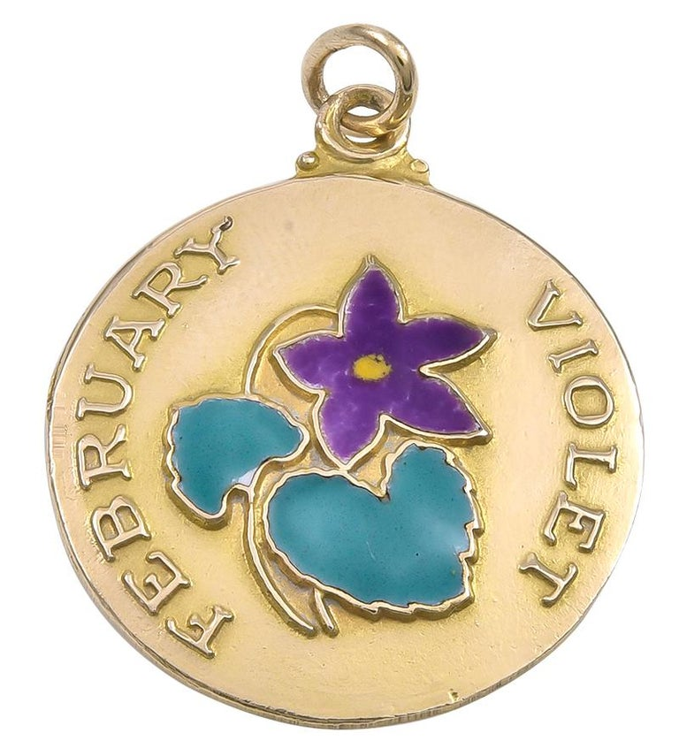 Lovely charm for a February baby:  a round disc with an applied enamel flower in the center.  Applied letters spell out