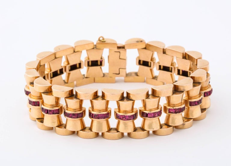 18k rose gold and calibre ruby bracelet. 74 grams hourglass shaped links each set with a channel of square rubies (5)  total 90 stones 5.00 carats