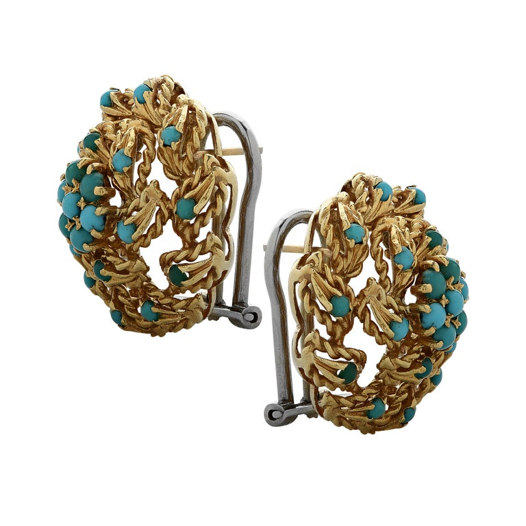 Beautiful stud earrings crafted in 18 karat yellow gold with turquoise cabochons. Turquoise cabochons arranged in a flower rest in the center of twisted gold leaves clustered together, swirling outwards, with turquoise cabochons sprinkled on the
