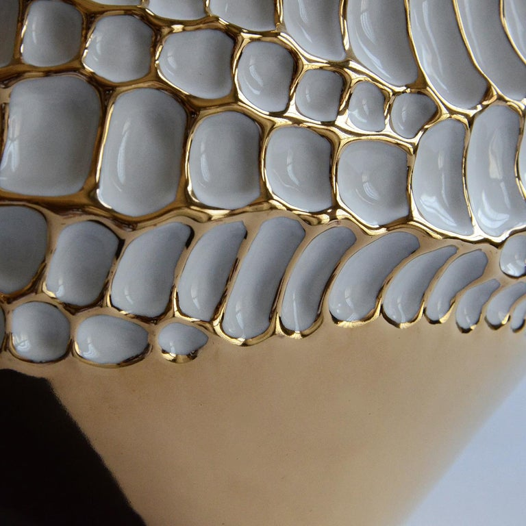 The particular elliptical shape and textured surface resembling hammering, are the result of a meticulous study on the microscopic magnification of a seed. This precious vase in glazed porcelain is decorated with gold 23-karat, applied by expert