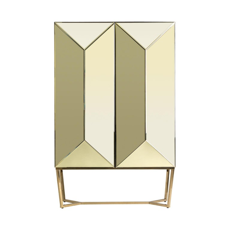 Gold bevelled mirror and gilded metal feet bar cabinet sparkling and sophisticated in an Art Deco style.