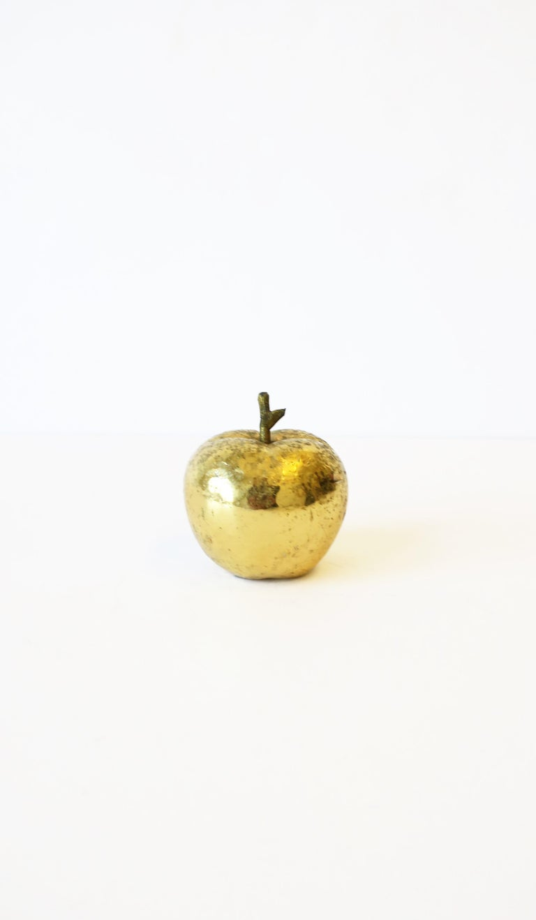 A substantial gold apple sculpture decorative object or paperweight. Apple has a bright and reflective gold exterior over bronze or brass with detailed stem. A cool piece for a desk or other area. Piece measures: 2