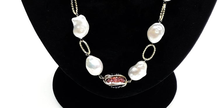 Refined necklace with 18K Gold chain. The necklace is characterized by river pearls alternated with red rubies and blue sapphires. High Italian gold craftsmanship. An ideal necklace for an summer evening.