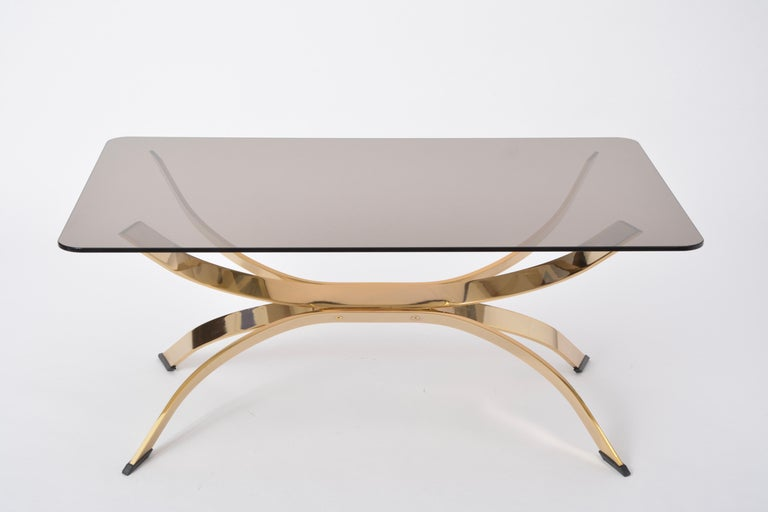 Gold Colored Mid-Century Modern coffee table with smoked Glass top  The table's base is made of gold colored metal, the top is made of smoked glass. The base is in excellent condition, the glass top is new.
