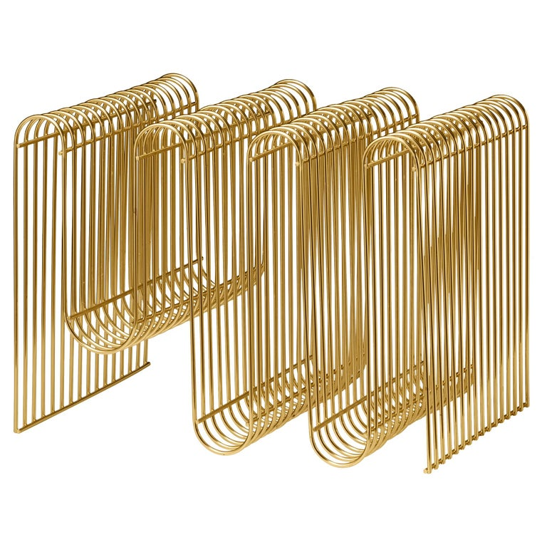 Gold contemporary magazine holder Dimensions: L 40.5 x W 30.3 x H 30.3 cm  Materials: Steel. Also available in Silver and Black. Please contact us for more information.    The design of the Curva magazine holder has become an instant icon. The