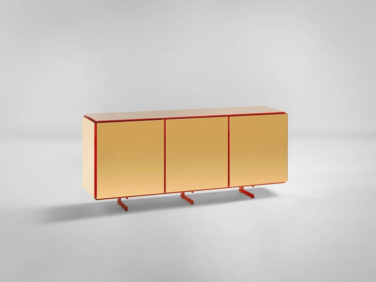 Sem Gold collection, three doors sideboard. Corallo lacquered wooden structure, gloss finish. Available more colorway variants. Plated external shell in 24-karat polished yellow gold combined with ultra-reflective steel. The Gold collection has a