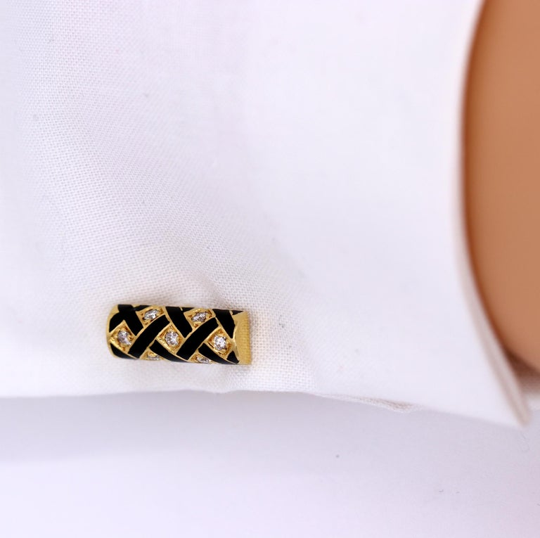 A gentleman's dress set, complete with a pair of cufflinks, and four buttons for a tuxedo shirt. The front of each cufflink has a black enamel lattice design, set with 7 round brilliant cut diamonds. The back of each cufflink is hinged for ease of
