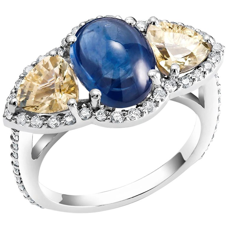 18 karat white gold cocktail ring Cabochon sapphire weighing 4.07 carat  Triangle yellow sapphire weighing 1.90 carat Surrounded by pave-set diamonds weighing 0.80 carat Diamond quality G VS New ring  Ring finger size 6 In Stock Ring can be resized