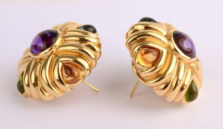 Bold and sporty 18 karat gold earrings with a central round amethyst slightly more than 9 mm in diameter. The corner stones are pear shaped aquamarines; garnets; citrines and peridots. The mix of colors makes them wearable with virtually everything.