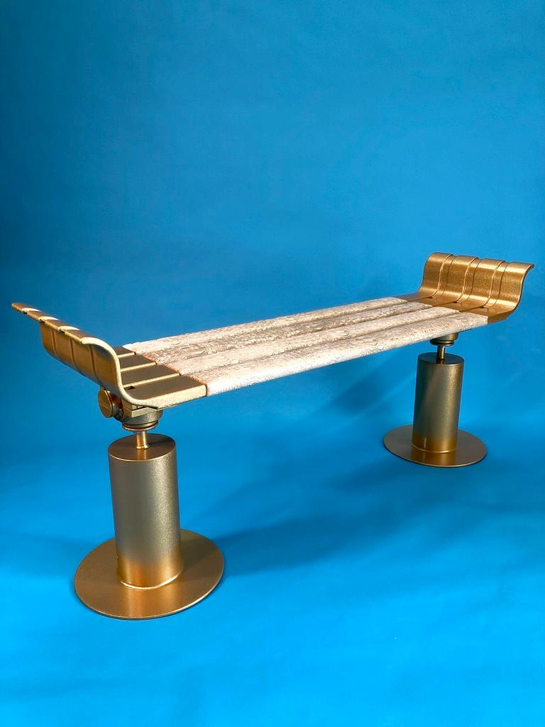 The Apollo bench is a unique single edition piece. Cast aluminum top with steel legs covered in a two stage powder coating. The base layer is metallic gold and the second layer is clear coat with gold metal flake. The iron wood and teak seat slats