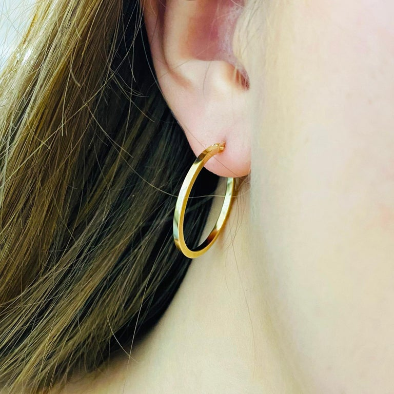 These stunning polished 14k yellow gold hoops provide a look that is both trendy and classic. While they were once worn by kings and queens to signify power and social status, hoop earrings are now considered a statement of unity and strength. Hoop