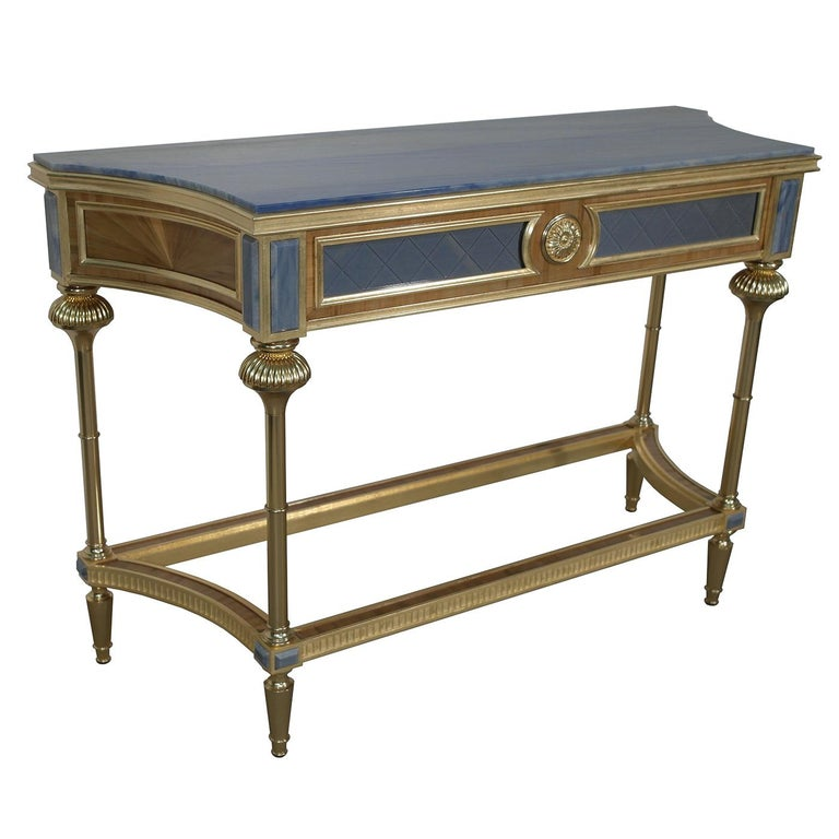This opulent wooden console table combines natural straw veneer details with 22-karat gold-plated brass accents. The 22-karat gold leaf details boast a white patina treatment for a vintage look. The front is upholstered in blue silk, topped with