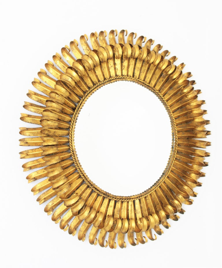 Lovely 1950s hand-hammered double layered eyelashed gilt iron sunburst mirror with gold leaf finish and circular shape. The frame is made by a double layer of curved beams in eyelash shape that makes the piece highly decorative. It has a beautiful