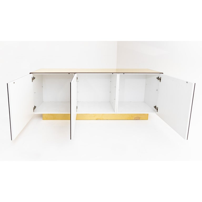 Three-door sideboard on a wide smooth base, covered on all sides with gold-tinted mirror panes. The interior is painted white and offers space for shelves (missing). The doors open by means of a push mechanism.
