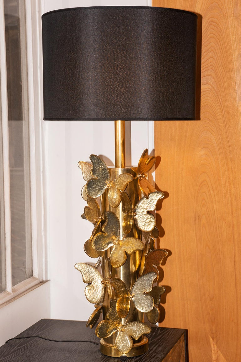 Table Lamp Gold Murano Butterflies with polished brushed brass base table lamp ornamented with murano glass butterflies with gold leaf taken under the murano glass. With black lamp shade included: Diameter 43cm. Table lamp base: Diameter 27cm,