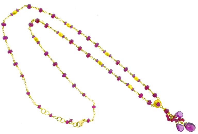 Ruby long chain in 22k gold, with an 18K clasp, 54 natural red rubies suspending a hassle of faceted deep pink natural tourmaline.  Approximately 13 cts of stones, the chain is 20 inches long and the pendant is 1.5 inches long.  This is a new piece