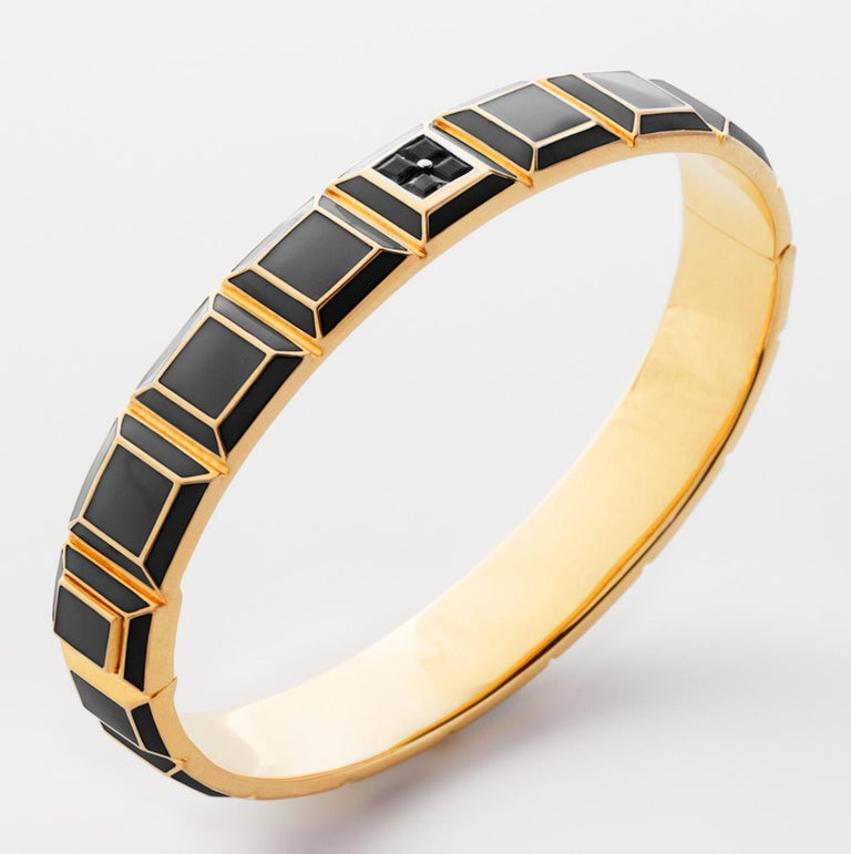 Gold-Plated Enamel Carousel Bracelet features a Yellow Gold-Plated Silver bracelet with Black Enamel and Black Diamonds, along with a clasp closure that secures the bracelet onto the wearer's wrist.  Yellow Gold-Plated Silver, Black Enamel, Black