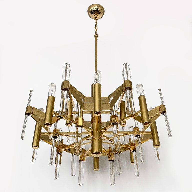 Large gold-plated brass twelve-light chandelier by Gaetano Sciolari. Polished gold plate and brushed brass design. Twenty 9.75