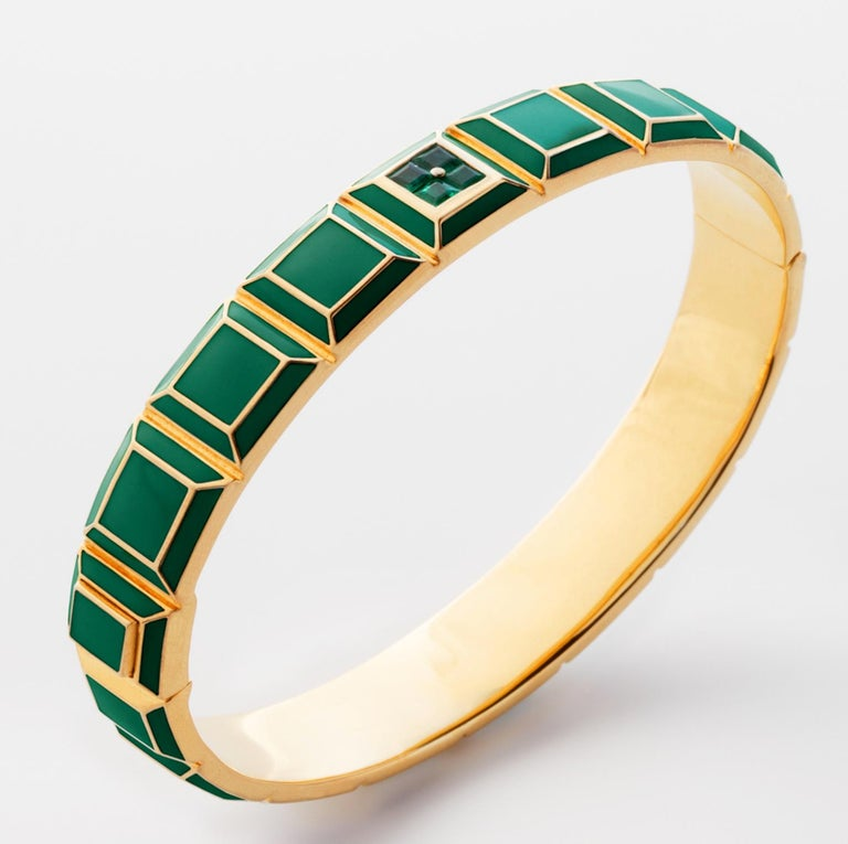 Gold-Plated Enamel Carousel Bracelet features a Yellow Gold Plated Silver bracelet with green enamel and emeralds, along with a clasp closure that secures the bracelet onto the wearer's wrist.  Yellow Gold Plated Silver, Green Enamel, Emeralds