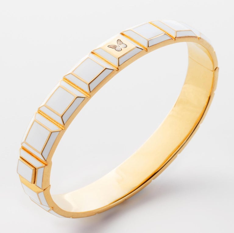 Gold-Plated Enamel Carousel Bracelet features a Yellow Gold Plated Silver bracelet with white enamel and butterfly engraving, along with a clasp closure that secures the bracelet onto the wearer's wrist.  Yellow Gold Plated Silver, White